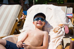 Cute little boy sunbathing at ocean beach Royalty Free Stock Image