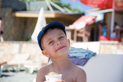 Cute little boy sunbathing at ocean beach Royalty Free Stock Photography