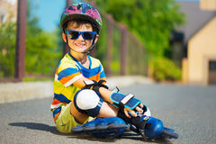 Cute little boy in sunglasses with rollers Stock Image