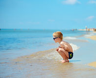 Cute little boy in sunglasses sitting at beach Royalty Free Stock Images