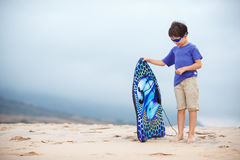 Cute little boy with surf board at the beach. During summer holiday vacation Stock Photos