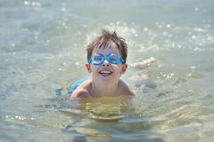 Cute little boy swimming in a shallow water Royalty Free Stock Images
