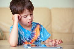 Cute little boy with a tablet pc Royalty Free Stock Images