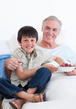 Cute little boy taking care of his grandfather Stock Photography