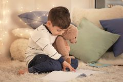 Cute little boy with teddy bear reading book. At home Royalty Free Stock Image
