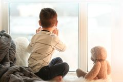 Cute little boy with teddy bear sitting on window sill. At home stock images