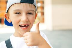 Cute little boy without teeth smiles outdoors. Portrait of fashionable little boy in baseball cap. Happy childhood