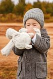 Little boy tenderly kisses his toy bunny with his eyes closed Royalty Free Stock Photos