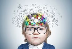 Cute little boy thinking. Adorable little boy wearing blue suit and glasses standing near gray wall with colorful brain sketch with cogs drawn inside his head royalty free stock photos