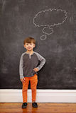 Cute little boy with a thought bubble on the blackboard Royalty Free Stock Images