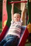 Cute little boy about to take a ride on a slide royalty free stock photography