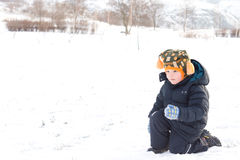 Cute little boy about to thow a snowball Royalty Free Stock Photos
