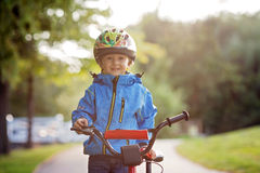 Cute little boy, toddler child, riding bike in a helmet. Back lit Stock Photography