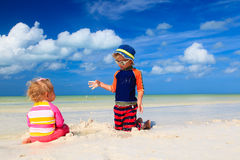 Cute little boy and toddler girl play on beach Stock Photography