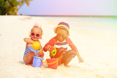 Cute little boy and toddler girl play with sand on beach Stock Images