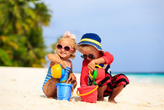 Cute little boy and toddler girl play with sand on royalty free stock images