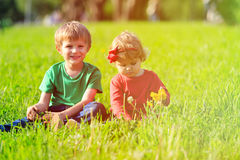 Cute little boy and toddler girl playing on green grass Stock Photos