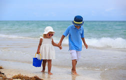 Cute little boy and toddler girl walk on beach Stock Photography
