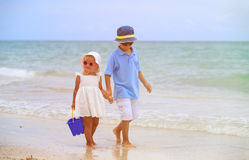Cute little boy and toddler girl walk on beach Stock Photo