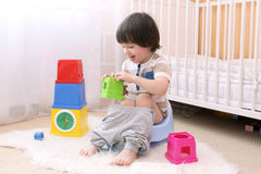 Cute little boy with toys sits on potty at home. Cute little boy sitting on potty at home royalty free stock photo