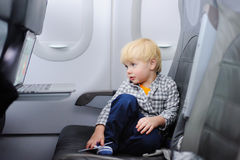 Cute little boy traveling by an airplane Stock Image