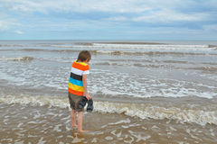 Cute little boy tries cold water in waves on beach. Kid trying cold sea water in waves on beach, with seascape in the background Stock Photos