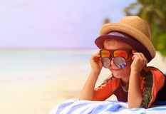 Cute little boy trying on sunglasses at beach Stock Image