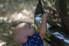Cute little boy is trying to unlock the car trunk. He just learned to walk and everything is interesting to him Royalty Free Stock Image