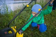 Cute little boy turn on a lawn mower. A cute little boy turn on a lawn mower Stock Images
