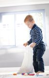 Cute little boy unpacking bag with toys Royalty Free Stock Photos
