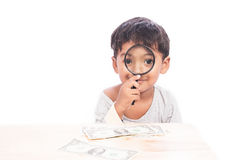 Cute little boy use magnifier looking money Stock Images