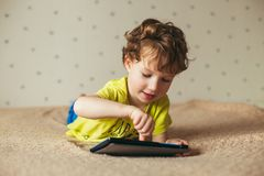 Free Cute Little Boy Using A Pad. Child Playing With Digital Tablet Lying On A Bed. Free Time. Tehnology And Internet Concept Stock Images - 109244804