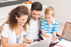 Cute little boy using laptop with his parents at table Royalty Free Stock Photos
