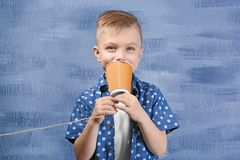 Cute little boy using plastic cup as telephone Stock Photography