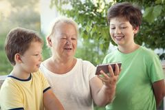 Cute little boy using smartphone with grandma at home veranda stock images