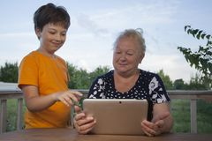 Cute little boy using tablet pc with grandma at home veranda stock photos