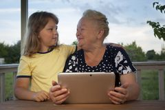 Cute little boy using tablet pc with grandma at home veranda royalty free stock photography