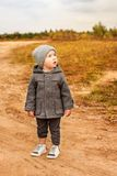 Cute little boy in a vintage clothes in the village stands and looks at the sky with his mouth open Stock Image