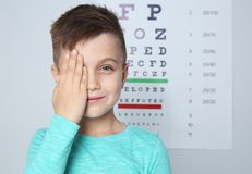 Cute little boy visiting children`s doctor, space for text. Eye examination royalty free stock image