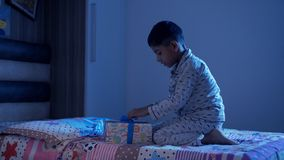 A cute little boy waking up early morning and opening his Christmas gift by Santa Claus
