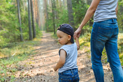 Cute little boy walking in park holding parents hand. Happy family and lifestyle concept Stock Image