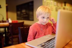 Cute little boy watching cartoon movie using computer in the cafe or restaurant. Child communication by social net or messenger. Using laptop. Kids online royalty free stock image