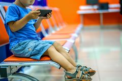 Cute little boy watching cartoons on smartphone in waiting room. Cute little boy watching cartoons on smartphone in empty waiting room royalty free stock photos