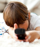Cute little boy watching TV lying on the floor. In the living-room Stock Photo