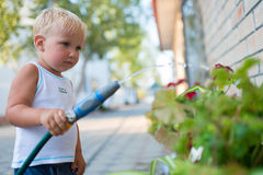 Cute little boy watering the flowers outdoor. Royalty Free Stock Image