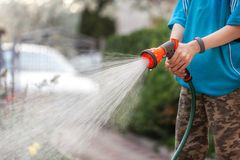 Cute boy watering plants from the hose, makes a rain in the garden. Child helping parents to grow flowers. Cute little boy watering plants from the hose, makes a royalty free stock photos