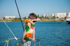 Cute little boy wearing sunglasses and Hawaiian decoration aboard Royalty Free Stock Image