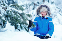 Cute little boy wearing warm clothes playing on winter forest Stock Photography