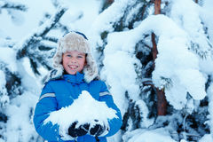 Cute little boy wearing warm clothes playing on winter forest Royalty Free Stock Photos