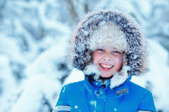 Cute little boy wearing warm clothes playing on winter forest Royalty Free Stock Photo
